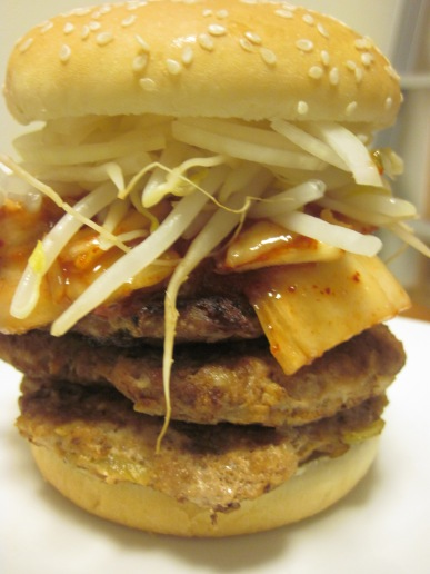 three burgers crowned with kimchi, onion, and steamed mung bean sprouts.